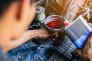 Pouring new transmission fluid into a car in Chicago, Illinois